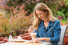 Beautiful woman drinking coffee. One the street stock photography