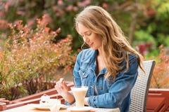 Beautiful woman drinking coffee. One the street stock image