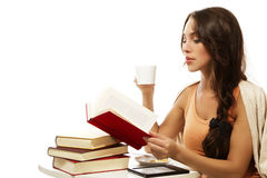 Beautiful woman drinking coffee while reading book Stock Photo