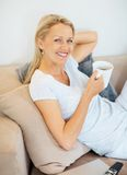 Beautiful woman drinking coffee relaxing on sofa Royalty Free Stock Photos