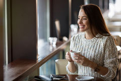 Beautiful woman drinking coffee in restaurant alone Stock Image