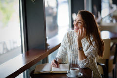 Beautiful woman drinking coffee in restaurant alone Royalty Free Stock Photos