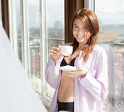 Beautiful woman drinking coffee sitting by the window royalty free stock photography