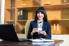 Beautiful woman drinking coffee at a table Royalty Free Stock Photos