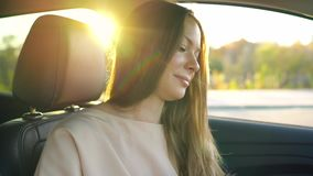 Woman speaks on the smartphone and drinks coffee in the car. Beautiful woman drinking coffee and talking on the smartphone in the car stock video