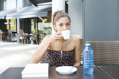Beautiful woman drinking coffee in the terrace restaurant. Royalty Free Stock Photography