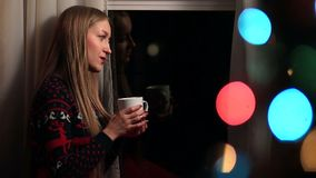 Beautiful woman drinking coffee on Xmas Eve stock video footage
