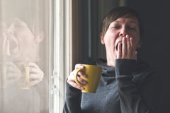 Beautiful Woman Drinking Coffee and Yawning Stock Photos