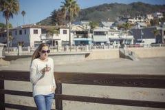 Beautiful woman drinking her morning coffee walking along boardwalk Royalty Free Stock Photo