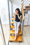 Beautiful woman drinking hot coffee sitting on stairs at home Stock Photos
