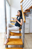 Beautiful woman drinking hot coffee sitting on stairs at home Royalty Free Stock Photo