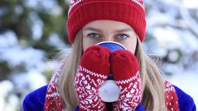 Beautiful woman drinking hot coffee in winter park stock footage