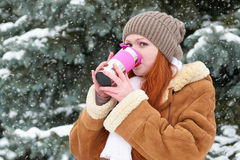 Beautiful woman drinking a hot drink and keep warm on winter outdoor, snowy fir trees in forest, long red hair, wearing a sheepski Stock Images