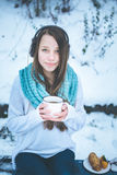 Beautiful woman drinking hot drink in winter park Royalty Free Stock Image