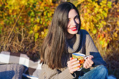 Beautiful woman drinking hot tea outdoors. Beautiful young woman in autumn forest getting warm with cup of hot tea Royalty Free Stock Image