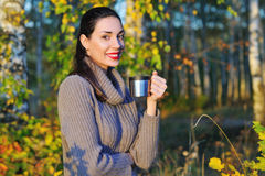 Beautiful woman drinking hot tea outdoors. Beautiful young woman in autumn forest getting warm with cup of hot tea from thermos jug Royalty Free Stock Photo
