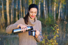 Beautiful woman drinking hot tea outdoors. Beautiful young woman in autumn forest getting warm with cup of hot tea from thermos jug Stock Images