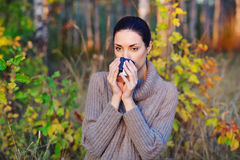 Beautiful woman drinking hot tea outdoors. Beautiful young woman in autumn forest getting warm with cup of hot tea from thermos jug Stock Photos
