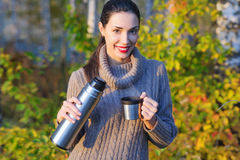 Beautiful woman drinking hot tea outdoors. Beautiful young woman in autumn forest getting warm with cup of hot tea from thermos jug Stock Photo