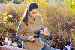 Beautiful woman drinking hot tea outdoors. Beautiful young woman in autumn forest getting warm with cup of hot tea from thermos jug Royalty Free Stock Images