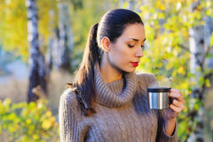 Beautiful woman drinking hot tea outdoors. Beautiful young woman in autumn forest getting warm with cup of hot tea from thermos jug Royalty Free Stock Photos