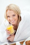 Beautiful woman drinking juice in bed Royalty Free Stock Photo