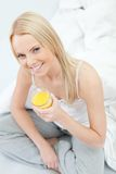 Beautiful woman drinking juice in bed Royalty Free Stock Photography