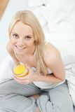 Beautiful woman drinking juice in bed Royalty Free Stock Photos