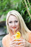 Beautiful woman drinking orange cocktail Royalty Free Stock Photos