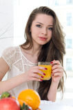 Beautiful woman is drinking orange juice Stock Photography