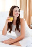 Beautiful woman drinking orange juice on bed Stock Images