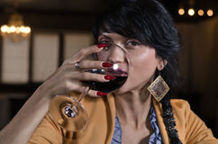 Beautiful woman drinking red wine in a bar Royalty Free Stock Images