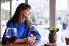 Beautiful woman drinking red wine with friends in restaurant, portrait with wine glass near window. Vocation holidays bar concept.  stock image