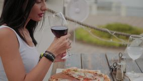 Beautiful woman drinking red wine on the terrace in a restaurant. Beautiful woman drinking red wine on the terrace in a restaurant stock video footage