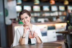 Beautiful woman drinking sweet drink in Cafe Royalty Free Stock Images