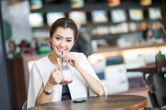 Beautiful woman drinking sweet drink in Cafe Stock Images