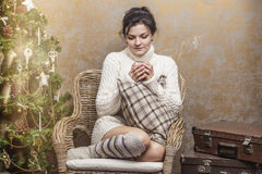 Beautiful woman drinking tea or coffee sitting in a chair in the Stock Images