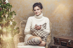 Beautiful woman drinking tea or coffee sitting in a chair in the Royalty Free Stock Photo