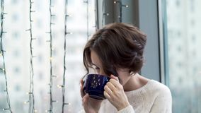 Beautiful woman drinking tea and looking out window with garlands. Winter warm comfort. Woman looks out window waiting. For arrival of loved one stock footage