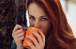 Beautiful woman drinking tea outdoor. From orange cup while looking to the camera. Natural light portrait in winter season Stock Photos