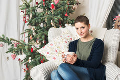 Beautiful woman drinking tea, sitting in front of xmas tree Stock Image
