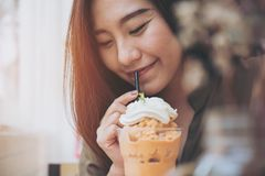 A beautiful woman drinking Thai tea milk shake and whipped cream on the top with straw. In vintage cafe stock images