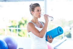 Beautiful woman drinking water while holding yoga mat Royalty Free Stock Photos