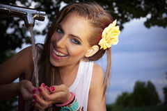 Beautiful woman drinking water in the park Stock Images