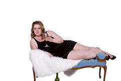 Beautiful Woman Drinking Wine on the Couch Royalty Free Stock Photography
