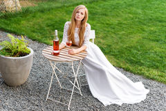 Beautiful woman drinking wine in outdoors cafe. Portrait of young blonde beauty in the vineyards having fun, enjoying a Royalty Free Stock Photography