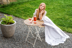 Beautiful woman drinking wine in outdoors cafe. Portrait of young blonde beauty in the vineyards having fun, enjoying a Stock Images