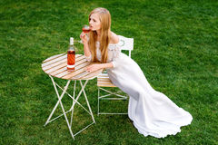 Beautiful woman drinking wine in outdoors cafe. Portrait of young blonde beauty in the vineyards having fun, enjoying a Stock Photo
