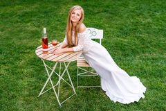 Beautiful woman drinking wine in outdoors cafe. Portrait of young blonde beauty in the vineyards having fun, enjoying a Royalty Free Stock Image