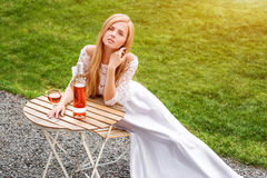Beautiful woman drinking wine in outdoors cafe. Portrait of young blonde beauty in the vineyards having fun, enjoying a Stock Image
